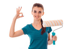 Beauty young slim builder girl makes renovations with paint roller and shows OK isolated on white background Royalty Free Stock Photos