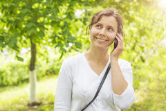 Beauty young smiling girl is calling by phone in green park Stock Photo