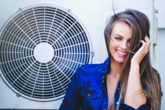 Beauty young woman with air conditioning. near the fan happy laughing. Long hair. Fashionable lady with a beautiful hairdo, makeup. Against the background of royalty free stock images