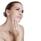 Beauty young woman applying face foundation stock photography