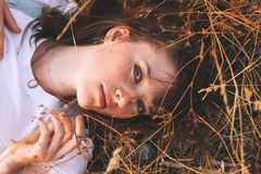 Beauty Young Woman with Brown Hair in Golden Field at Sunset. Stock Photography