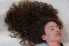 Girl lying with long curly hair arranged in a mane with white shirt stock photography
