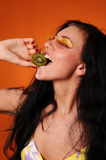 Beauty young woman eat kiwi Stock Images