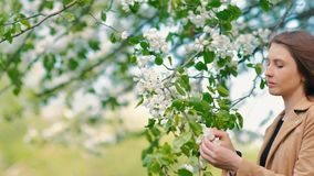 Beauty young woman enjoying nature in spring apple orchard, Happy Beautiful girl in Garden with blooming trees. Aroma stock video footage