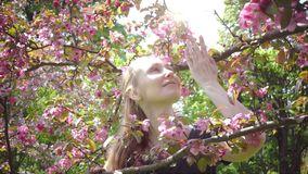 Beauty young woman enjoying nature in spring apple orchard, happy beautiful girl in garden with blooming apple trees. Smiling Person smelling blossom flowers stock video footage