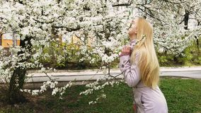 Beautiful girl on the flower trees background. Beauty young woman enjoying nature in spring , Happy Beautiful girl in Garden with blooming trees. Slow motion stock video footage