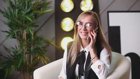 Beauty young woman in glasses siting in the office with telephone, talking and writing in the notebook. Plants on the. Background. Business and education stock footage