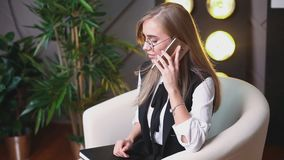 Beauty young woman in glasses siting in the office with telephone, talking and writing in the notebook. Plants on the. Background. Business and education stock video footage