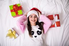 Beauty young woman in her bed at home in Christmas wear and santa hat with gift view from top. Beauty young woman in her bed at home in Christmas wear and santa Royalty Free Stock Images
