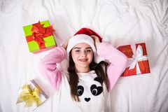 Beauty young woman in her bed at home in Christmas wear and santa hat with gift view from top. Beauty young woman in her bed at home in Christmas wear and santa Stock Photos