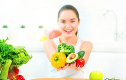 Beauty young woman holding fresh vegetables and fruits in her kitchen at home. Healthy eating concept stock photo