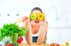 Beauty young woman holding fresh vegetables and fruits in her kitchen at home Royalty Free Stock Photography