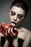 Beauty young woman licks blood from human heart Royalty Free Stock Photos