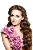 Beauty young woman, luxury long curly hair with orchid flower. H. Aircut. Beautiful girls fresh healthy skin, makeup, lips, eyelashes. Fashion model in spa care Royalty Free Stock Photos