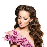 Beauty young woman, luxury long curly hair with orchid flower. H Royalty Free Stock Photo