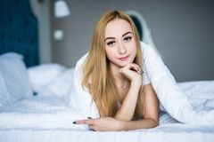 Beauty young woman lying under a duvet in a bedroom. Blonde woman lying under a duvet in a bedroom stock photo