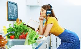 Beauty young woman prepare breakfast in kitchen. Music listening Stock Photos