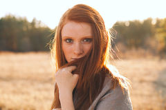 Beauty Young Woman with Red Hair in Golden Field at Sunset. Stock Photos