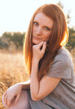 Beauty Young Woman with Red Hair in Golden Field at Sunset. Royalty Free Stock Images