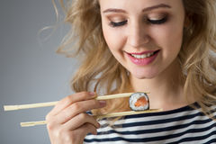 Beauty young woman with  rolls Japanese food Stock Photos