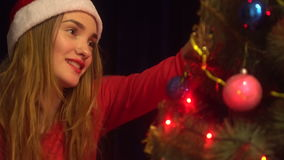 Beauty young woman in santa hat smiling and dacorates a christmas tree stock video footage