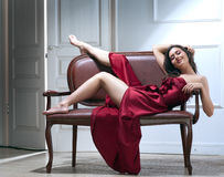 Beauty young woman on sofa Stock Images