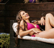 Beauty young woman after spa in bikini and robe at hotel resort, on terrace enjoying warm sun Royalty Free Stock Image