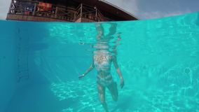Beauty young woman swimming under water in outdoor pool. Beauty young woman swimming underwater in outdoor swimming pool in hotel. Slow motion video footage 4k stock video footage