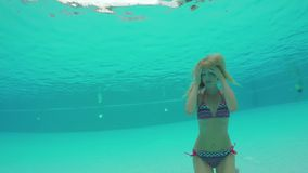 Beauty young woman swimming under water in outdoor pool. Beauty young woman swimming underwater in outdoor swimming pool in hotel. Slow motion video footage 4k stock footage