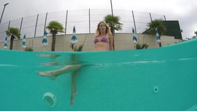 Beauty young woman swimming under water in outdoor pool. Beauty young woman swimming underwater in outdoor swimming pool in hotel. Slow motion video footage 4k stock video