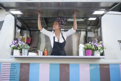 Beauty and young woman works in a food truck. Beautiful and young woman working on a food truck stock photo