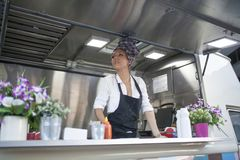 Beauty and young woman works in a food truck. Beautiful and young women working on a food truck stock photography