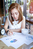 Beautyful Asia business woman working. In a cafe with graph and paper sheet stuff Royalty Free Stock Image