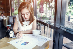 Beautyful Asia business woman working. In a cafe with graph and paper sheet stuff Royalty Free Stock Images