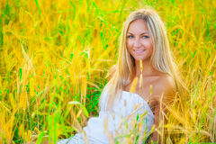 A beautyful blond sitting in the wheat Royalty Free Stock Photos