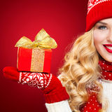 Beautyful blond woman with christmas box gift on red background. Royalty Free Stock Photography