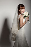 A beautyful bride holding her bouquet from roses and smiling. Dark background Royalty Free Stock Photography