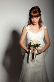 A beautyful bride looks down at her bouquet from roses. Dark background Stock Photography