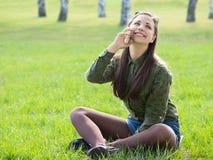 Beautyful dziewczyna opowiada na telefonu obsiadaniu na świeżej trawie Zdjęcia Royalty Free