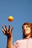 Beautyful flicka som kastar orangen i luft royaltyfria bilder
