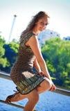 Beautyful Frau, die auf Geländer sitzt Stockfotografie