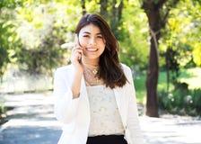 Beautyful-Geschäftsfrau, die intelligentes Telefon im Park geht und verwendet stockfotos