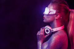 Beautyful girl with glitter and sparkles on her face and body. Portrait of TDJ with headphones and neon sunglasses