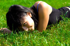 Beautyful girl on grass. Young beautyful girl lying on grass on a sunny day in a park Stock Photos