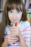 Beautyful girl holding many pencils. Royalty Free Stock Photos