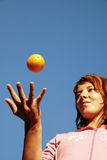 Beautyful girl throwing orange in air Royalty Free Stock Images
