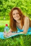 Beautyful redhead girl on grass with bottle of water Stock Image