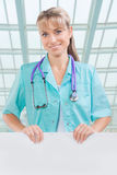Beautyful toothy smiling female doctor with white placard Stock Photography