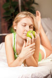 Beautyful woman with green apple. In bed Stock Images