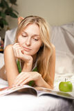 Beautyful woman with green apple. In bed Royalty Free Stock Image